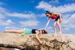 Muchachas que abrazan la playa del árbol Imagen de archivo libre de regalías