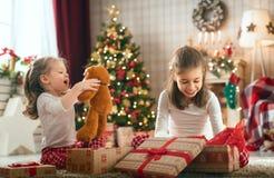 Muchachas que abren los regalos de la Navidad fotos de archivo libres de regalías
