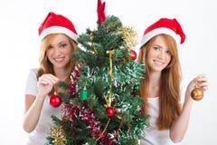 Muchachas que adornan el árbol de navidad Imagen de archivo libre de regalías