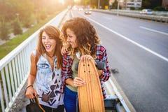 Muchachas que andan en monopatín sonrientes que se sientan en la calle que cuelga hacia fuera Fotografía de archivo
