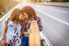 Muchachas que andan en monopatín sonrientes que se sientan en la calle que cuelga hacia fuera Foto de archivo