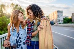 Muchachas que andan en monopatín sonrientes que se sientan en la calle que cuelga hacia fuera Imágenes de archivo libres de regalías