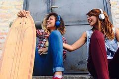Muchachas que andan en monopatín sonrientes que se sientan en la calle que cuelga hacia fuera Fotos de archivo libres de regalías