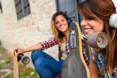 Muchachas que andan en monopatín sonrientes que se sientan en la calle que cuelga hacia fuera Fotografía de archivo libre de regalías