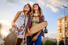 Muchachas que andan en monopatín sonrientes que se sientan en la calle que cuelga hacia fuera Imagen de archivo libre de regalías