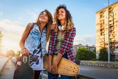 Muchachas que andan en monopatín sonrientes que se sientan en la calle que cuelga hacia fuera Fotos de archivo