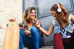Muchachas que andan en monopatín sonrientes que se sientan en la calle que cuelga música hacia fuera que escucha Fotografía de archivo