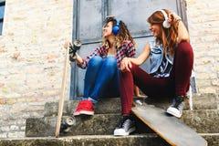 Muchachas que andan en monopatín sonrientes que se sientan en la calle que cuelga música hacia fuera que escucha Fotos de archivo