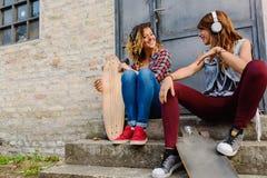 Muchachas que andan en monopatín sonrientes que se sientan en la calle que cuelga música hacia fuera que escucha Imagen de archivo