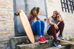 Muchachas que andan en monopatín sonrientes que se sientan en la calle que cuelga música hacia fuera que escucha Fotografía de archivo libre de regalías