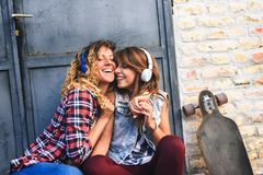 Muchachas que andan en monopatín sonrientes que se sientan en la calle que cuelga música hacia fuera que escucha Imagen de archivo libre de regalías
