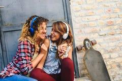 Muchachas que andan en monopatín sonrientes que se sientan en la calle que cuelga música hacia fuera que escucha Foto de archivo