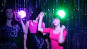 Muchachas que bailan en un partido en una luz colorida almacen de video
