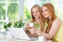 Muchachas que beben té con el ordenador portátil Fotografía de archivo libre de regalías