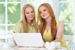 Muchachas que beben té con el ordenador portátil Imagen de archivo