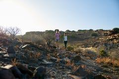 Muchachas que caminan abajo de la trayectoria de la montaña rocosa Fotos de archivo libres de regalías