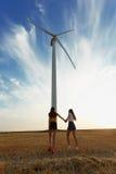 Muchachas que caminan al lado de un molino de viento Molino de viento eléctrico en el campo en un fondo soleado del cielo concept foto de archivo libre de regalías