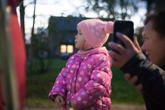 Muchachas que caminan con su hija en la ciudad de la tarde y el hablar en la comunicación video con su padre foto de archivo libre de regalías