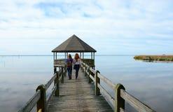 Muchachas que caminan en el embarcadero en el lago Foto de archivo libre de regalías