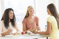 Muchachas que comen bocados en cantina de universidad Fotografía de archivo libre de regalías