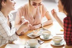 Muchachas que comen la torta y que beben el café en el café, descanso para tomar café Foto de archivo libre de regalías