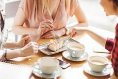 Muchachas que comen la torta y que beben el café en el café, descanso para tomar café Fotos de archivo libres de regalías