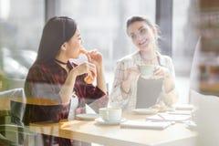 Muchachas que comen los cruasanes y que beben el café en el café, descanso para tomar café Imagenes de archivo