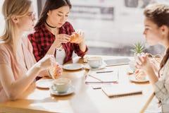 Muchachas que comen los cruasanes y que beben el café en el café, descanso para tomar café Foto de archivo libre de regalías