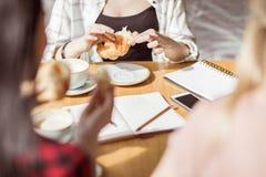 Muchachas que comen los cruasanes y que beben el café en el café, descanso para tomar café Fotos de archivo libres de regalías