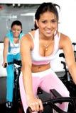 Muchachas que completan un ciclo en la gimnasia Foto de archivo libre de regalías