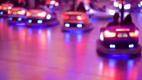Muchachas que conducen los coches de parachoques - parque de atracciones en la ciudad de la noche almacen de metraje de vídeo