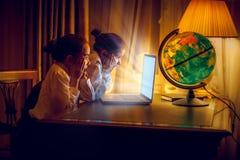 Muchachas que consideran con el asombro el ordenador portátil la noche Foto de archivo libre de regalías