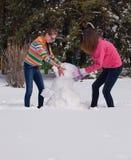 Muchachas que construyen un muñeco de nieve Foto de archivo libre de regalías