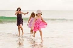 3 muchachas que corren en playa del océano apuntalan el agua hacia cámara Imagen de archivo