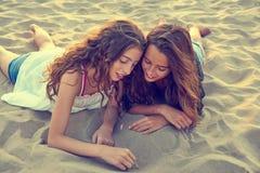 Muchachas que dibujan el finger en la arena de la playa en el verano Imagen de archivo libre de regalías