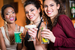 Muchachas que disfrutan de la vida nocturna en un club, cócteles de consumición Fotografía de archivo