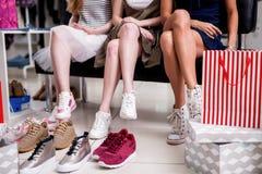 Muchachas que eligen los zapatos adolescentes rodeados por el calzado de la juventud en la tienda de moda de la ropa Fotos de archivo libres de regalías