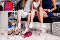 Muchachas que eligen los zapatos adolescentes rodeados por el calzado de la juventud en la tienda de moda de la ropa Fotos de archivo