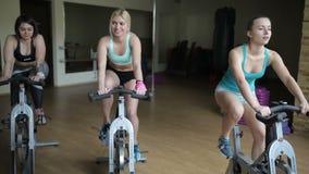 Muchachas que entrenan en las bicicletas estáticas en el gimnasio metrajes