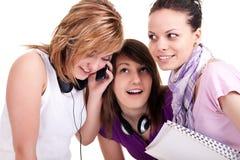 Muchachas que escuchan el móvil curiosamente Fotos de archivo libres de regalías