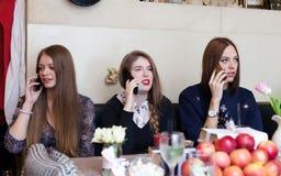 Muchachas que hablan en el teléfono celular en cafetería Imagen de archivo