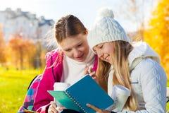Muchachas que hablan la mirada con el libro de texto Imagen de archivo
