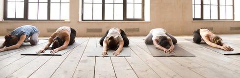 Muchachas que hacen actitud del niño durante la sesión de la yoga fotos de archivo