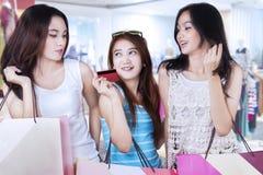 Muchachas que hacen compras con la tarjeta de crédito en la alameda Fotografía de archivo
