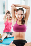 Muchachas que hacen estirando ejercicios en el gimnasio Imagenes de archivo