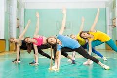 Muchachas que hacen estirando ejercicios en pasillo de deportes Foto de archivo libre de regalías