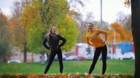 Muchachas que hacen la gimnasia en el parque Otoño Temporada de otoño almacen de video
