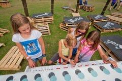 Muchachas que hacen música y que juegan el piano en un patio verde Fotografía de archivo libre de regalías