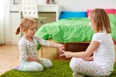 Muchachas que juegan al juego del piedra papel o tijera en casa imágenes de archivo libres de regalías