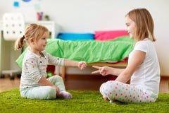 Muchachas que juegan al juego del piedra papel o tijera en casa imagen de archivo